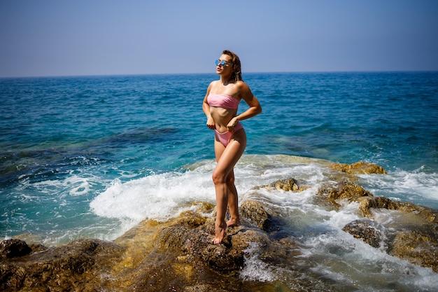 波を背景に晴れた日に岩のビーチで水着姿の美しい若い女性。夏の休暇。セレクティブフォーカス