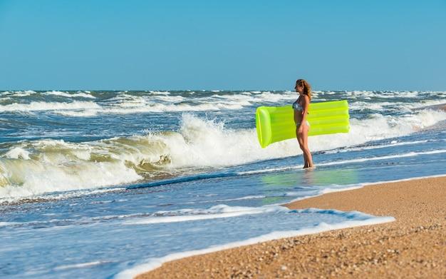 水着姿の美しい若い女性が手にエアマットレスを持ってビーチを走る
