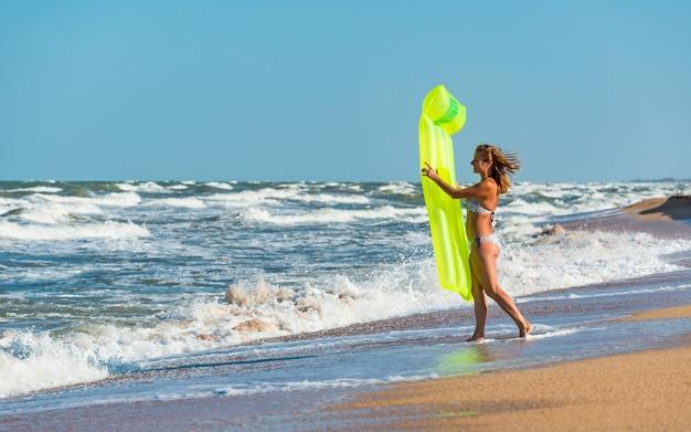 Красивая молодая женщина в купальнике бежит по пляжу с надувным матрасом в руках