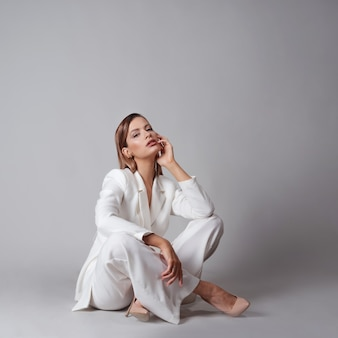 トレンディな白いスーツとベージュのハイヒールの靴で美しい若い女性