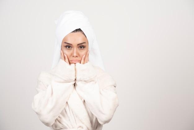 흰 벽에 포즈 흰 가운에 아름 다운 젊은 여자