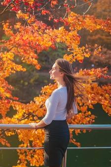 秋の公園で白いブラウスに美しい若い女性。湖と木がある公園の女性の肖像画。