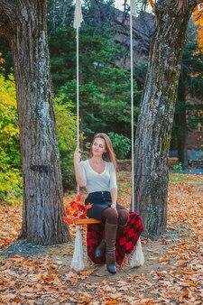 秋の公園で白いブラウスに美しい若い女性。ブランコに座っている公園で若い女性