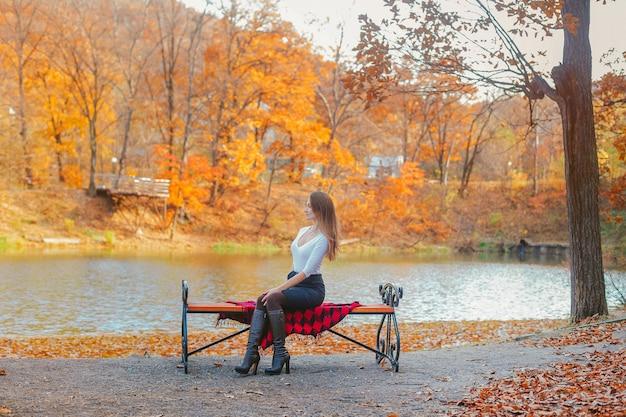 秋の公園のベンチに白いブラウスの美しい若い女性が座っています。湖と木がある公園の女性の肖像画。