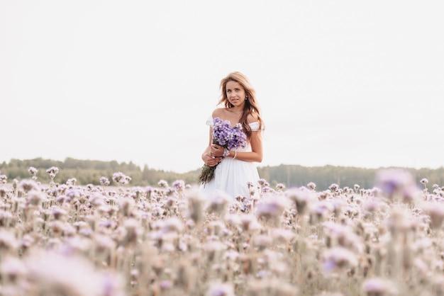 Красивая молодая женщина в белом платье с букетом цветов в поле летом на природе