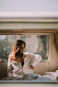 집에 있는 침실에 흰 셔츠를 입은 아름다운 젊은 여성