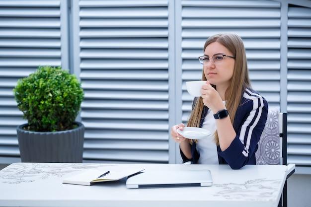 Красивая молодая женщина в белой футболке пьет кофе и работает на ноутбуке и улыбается, сидя на открытом воздухе в кафе. ноутбук молодой женщины для работы. женский фрилансер, работающий на ноутбуке