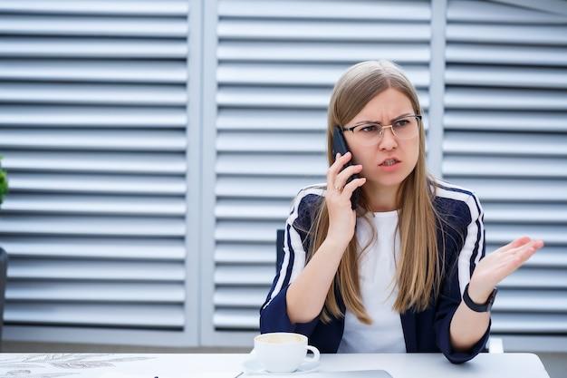 白いtシャツを着た美しい若い女性がコーヒーを飲んでいて、頭痛がして、ラップトップで働いて、カフェで屋外に座っています。仕事のための若い女性のラップトップ。ビジネス上の問題