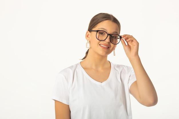 안경을 쓰고 흰색 배경에 흰색 티셔츠에 아름 다운 젊은 여자