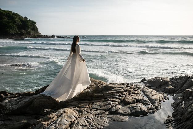 白いウェディングドレスを着た美しい若い女性