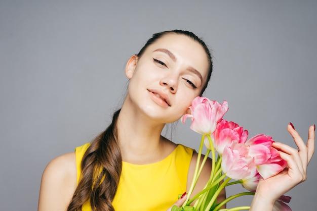 봄 날씨를 즐기는 노란 드레스를 입은 아름다운 젊은 여성, 향기로운 분홍색 꽃 꽃다발을 들고