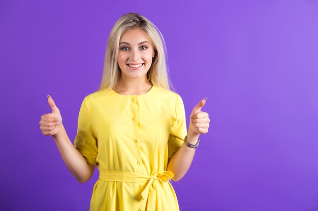 手ジェスチャーで黄色のドレスで美しい若い女性