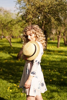 Красивая молодая женщина в яблоневом саду в весенний солнечный день - счастливые моменты