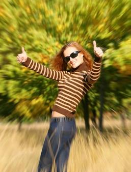 확인 표시를 보여주는 가을 공원에서 아름 다운 젊은 여자