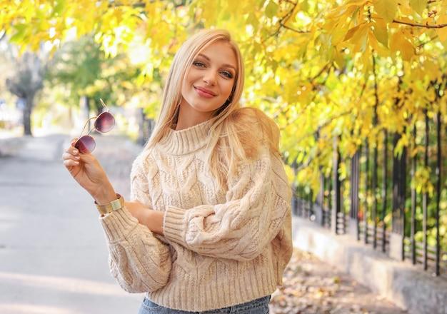 秋の公園の美しい若い女性