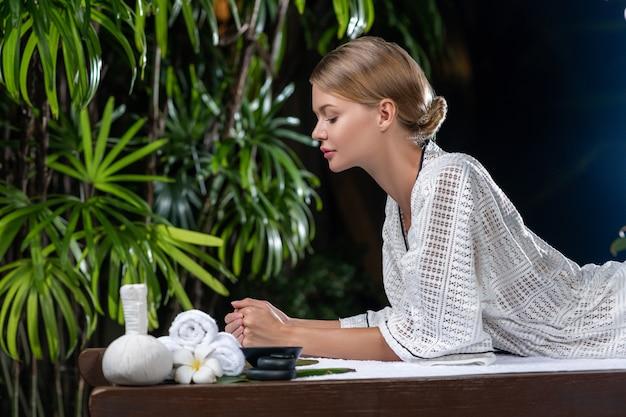 マッサージを待っているテーブルでリラックスしたバスローブの美しい若い女性。スパとケア