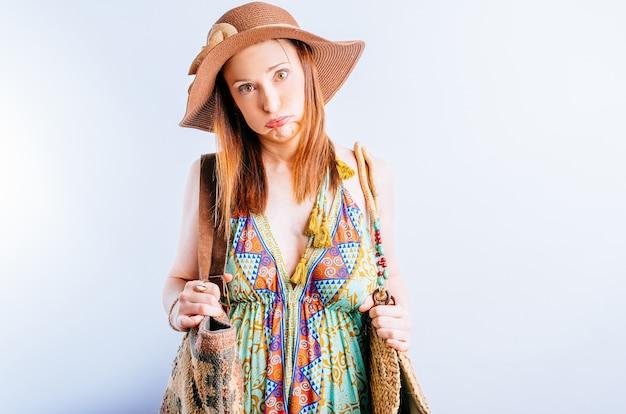 부푸는 가방과 함께 해변 모자 sundress에 아름 다운 젊은 여자. 여름 방학의 개념 문제