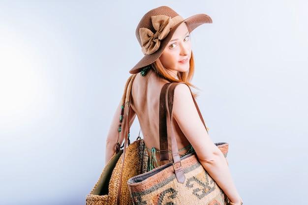 バッグとビーチ帽子の日よけ帽の美しい若い女性は、コピースペースで正面を向いて後ろを向いた。夏休みのコンセプト。ファッション
