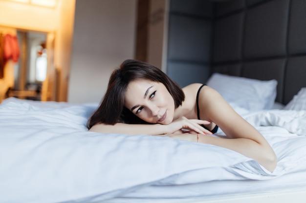 Красивая молодая женщина в постели рано утром
