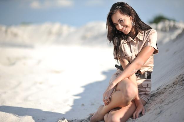 Красивая молодая женщина в летней одежде biege на песке