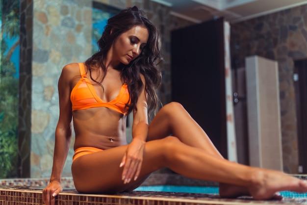 Красивая молодая женщина в бикини, сидя на краю бассейна