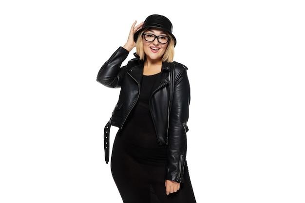 흰색 스튜디오 배경에 격리된 세련된 검은색 옷을 입은 아름다운 젊은 여성