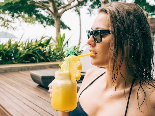 수영장 근처 일광욕용 침대에서 휴식을 취하는 동안 칵테일을 마시는 검은 비키니를 입은 아름다운 젊은 여성