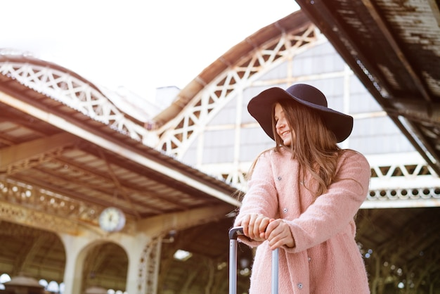 검은 모자와 가방이 달린 분홍색 코트를 입은 아름다운 젊은 여성이 역 플랫폼에 서 있습니다.