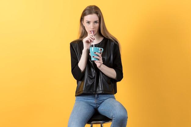 黒のジャケットとジーンズの美しい若い女性は椅子に座って、カップから飲む