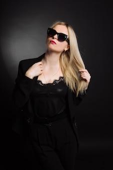 黒のジャケットと黒の背景にサングラスの美しい若い女性。かなりブロンドの女の子