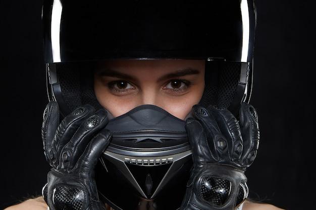黒革の手袋と保護バイクのヘルメットの美しい若い女性。転倒や事故から手と体を保護する魅力的な自己決定の女性のオートバイレーサー