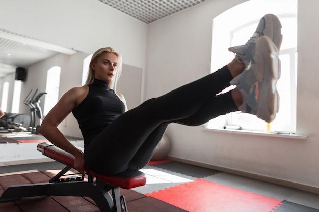 Красивая молодая женщина в черной стильной спортивной одежде в белых кроссовках сидит на тренажере и выполняет упражнения для мышц живота