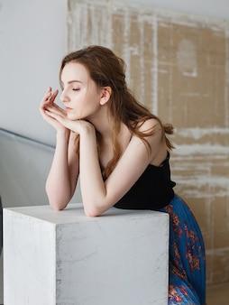 黒のトップ、青いスカート、かわいい思いやりのあるモデルの屋内の肖像画の美しい若い女性。スタジオでポーズをとる自然なきれいな女性
