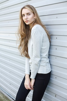 ブラウス、黒のジーンズの美しい若い女性。プロファイルシートで作られた壁でポーズをとるかわいい魅力的なモデル