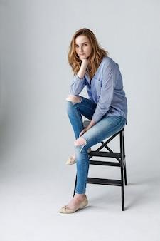 青い縞模様のシャツと破れたジーンズの美しい若い女性、かわいい思慮深いモデルの屋内の肖像画。木製のはしごでスタジオでポーズをとる自然な女性
