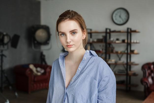 青い縞模様のシャツを着た美しい若い女性、かわいい思いやりのあるモデルの屋内の肖像画。