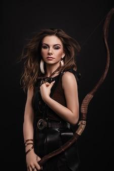 自由奔放に生きる服と弓と革のスカートの美しい若い女性