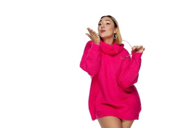흰색 스튜디오에 격리된 밝은 분홍색 편안한 스웨터 긴 소매를 입은 아름다운 젊은 여성