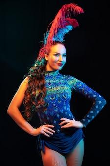 Красивая молодая женщина в карнавальном и маскарадном костюме в красочных неоновых огнях на черном