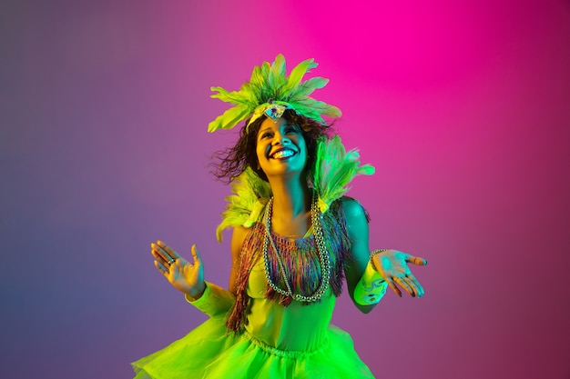 カーニバルとネオンの光の勾配で仮面舞踏会の衣装を着た美しい若い女性