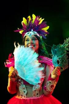 カラフルな光のカーニバルマスクと仮面舞踏会の衣装で美しい若い女性