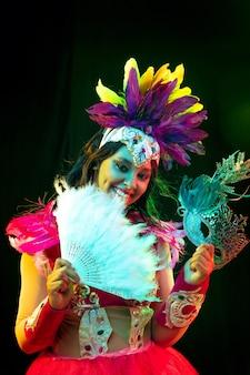 カラフルなライトでカーニバルマスクと仮面舞踏会の衣装で美しい若い女性