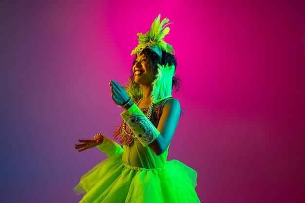 카니발에서 아름 다운 젊은 여자, 네온 그라데이션 벽에 춤 깃털을 가진 세련 된 무도회 의상 무료 사진