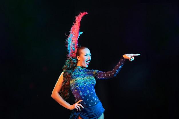 카니발에서 아름 다운 젊은 여자, 네온 불빛에 검은 벽에 깃털을 가진 세련된 무도회 의상
