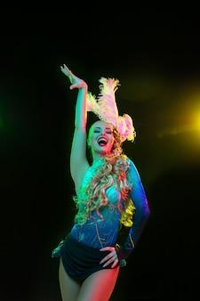 カーニバルの美しい若い女性、ネオンの光の黒い壁に羽を持つスタイリッシュな仮面舞踏会の衣装