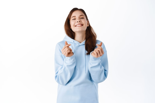 カジュアルな青いパーカーの美しい若い女性、指の心を示し、正面にかわいい笑顔、前向きな感情の概念、白い壁の上に立って