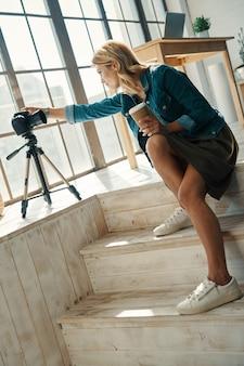 디지털 카메라 앞에서 작업하는 동안 장비를 조정하는 캐주얼 의류에 아름 다운 젊은 여자