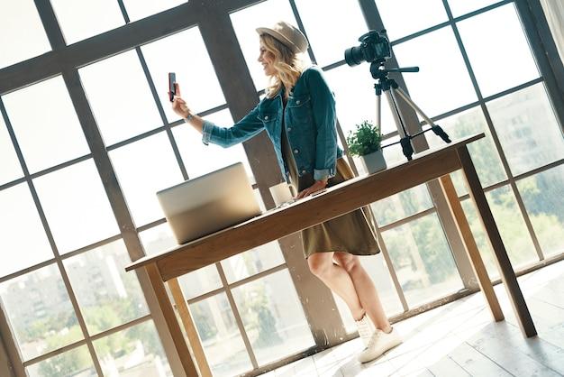 전화를 사용하여 셀카를 만들고 디지털 카메라 앞에 서있는 동안 웃고 캐주얼 의류에 아름 다운 젊은 여자