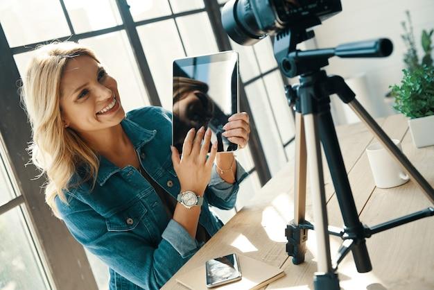 태블릿을 가리키고 디지털 카메라 앞에 앉아있는 동안 웃고 캐주얼 의류에 아름 다운 젊은 여자