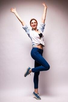 白の上に腕を上げるカジュアルウェアの美しい若い女性